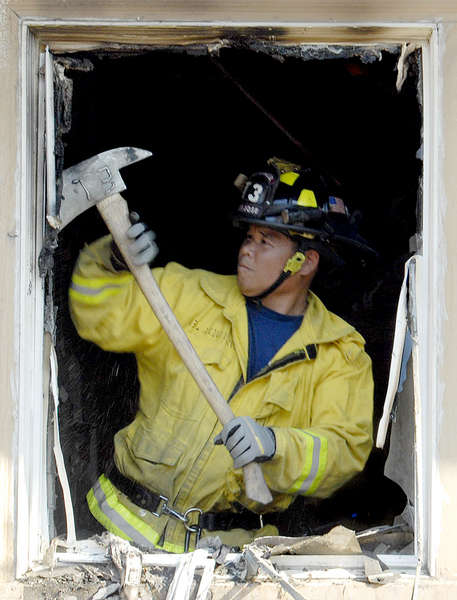A San Jose firefighter cleans up a wrecked window after a fire destroyed part of the house.