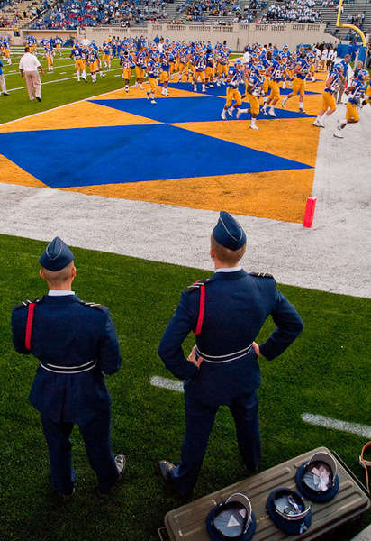 Military service men watching the football game on Spartan field.