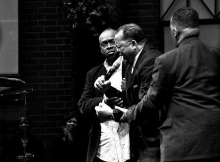 Bishop George W. Brooks is held down by two members of his congregation, during a passionate preach during a  service.
