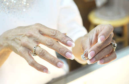 Angela Chamis, 49, Tim Stoll's fiancee, shows a display ring to a customer. She wears the rings that Tim made for her as gifts during their courtship and pending nuptials.