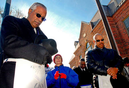 Bobby Bell, 59 (left) and Herald Wilson, 45 (right), members of the Masonic Lodge, bow their heads during a prayer outside the Motsville town square. Bell lead a march with other members of his lodge  for a special Martin Luther King Jr. celebration service.