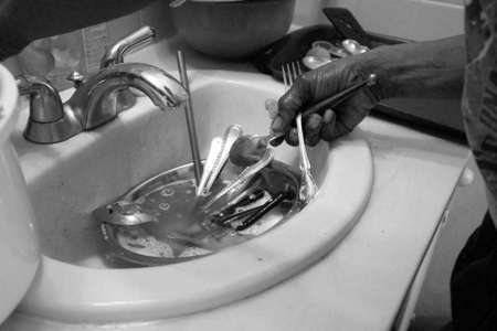 With no kitchen sink to clean her family's dishes, Denise uses the motel room's bathroom sink to wash and dry their silverware.