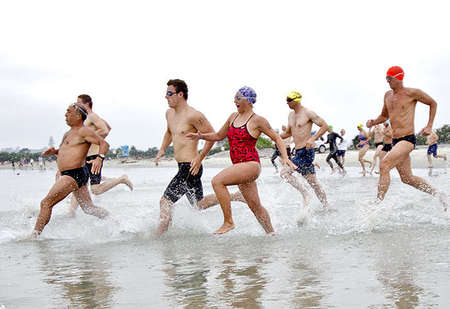 Participants of the swim master triathlon race to the water.