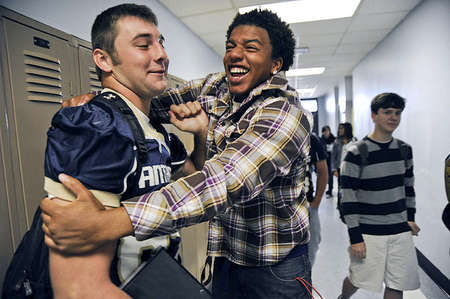 Titus Sublet, 19, embraces Mitchell Henry, left, to wish him luck before the big homecoming game. Titus is a recent graduate of Elizabethtown High School and now attends Elizabethtown Community & Technical College. He used to be a part of the EHS football team and is still good friends with Mitchell.