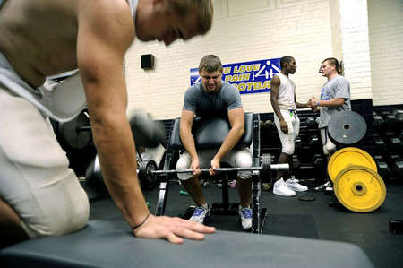 Mitchell Henry, center, takes on 120 pounds during football training. Mitchell, like his teammates at Elizabethtown High School, is expected to incorporate a high-speed and heavy-weightlifting workout in his routines. The football team's goal: keep its strength throughout the season, something Mitchell takes very seriously because of his college football aspirations.
