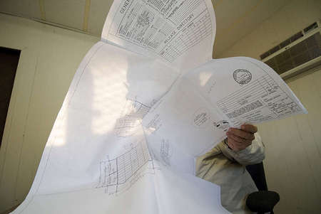 D.S.A. Inspector Don Williams reviews DSA approved documents before his early on-site construction inspection.