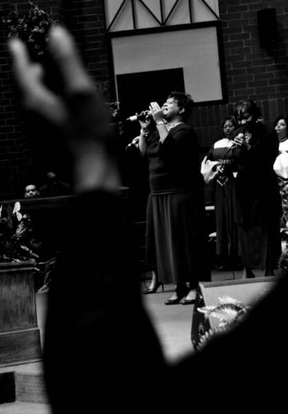 "The ""Heavenly Women"" ensemble, lead Zola Johnson, sings at the alter during a service."