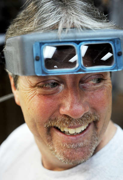 Tim Stoll, 51, smiles back at Angela during an exchange of jokes at the shop. He uses his goggles to examine jewelry.