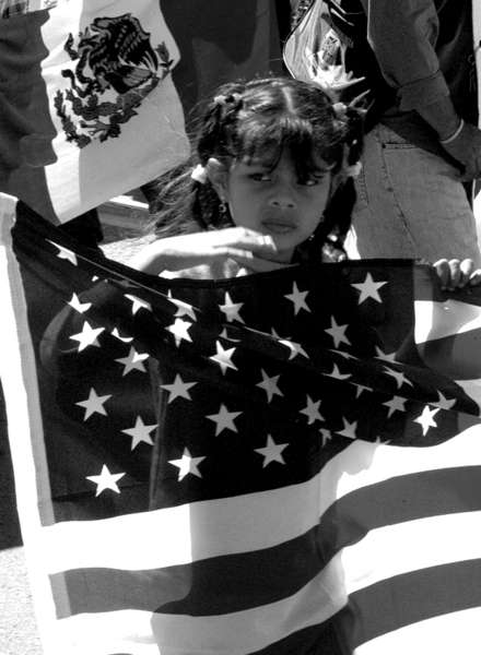 A girl marches with a U.S. flag at hand during a May 1st march.