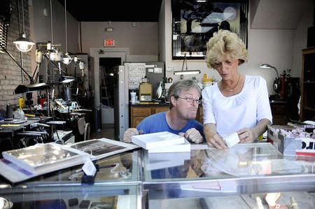 Tim and Angela check their inventory before they place the jewelry in front of the glass counter at Stoll's Custom Jewelers. Stoll's usually displays retail-made rings alongside Tims original designs.
