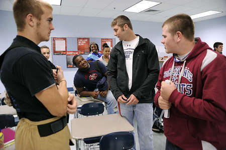 Mitchell Henry, center right, discusses football with his classmates during a break from their business class. Mitchell usually finds himself in the spotlight, even when he does not look for it.