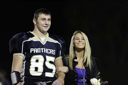 Hillari Caso, right, 17, is escorted by Mitchell Henry during the halftime of the homecoming football game. Hilari said Mitchell, who she considers a friend, is a sweet guy and loves his personality.