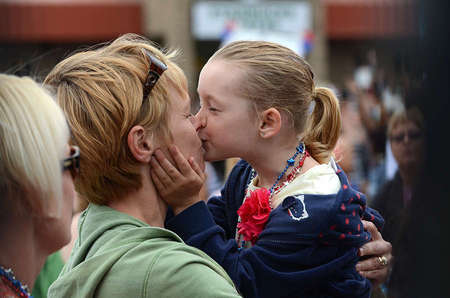 As Jessica Newman, 5, waited for her father to come down from the USS Vinson carrier, she kissed her mother out of excitement.